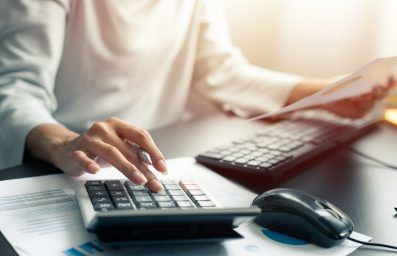 Woman accountant or banker use calculator and computer on table